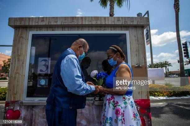 Michael Davis puts the ring on his bride Natasha during their wedding ceremony officiated by a clerk recorder at the Honda Center parking lot on...