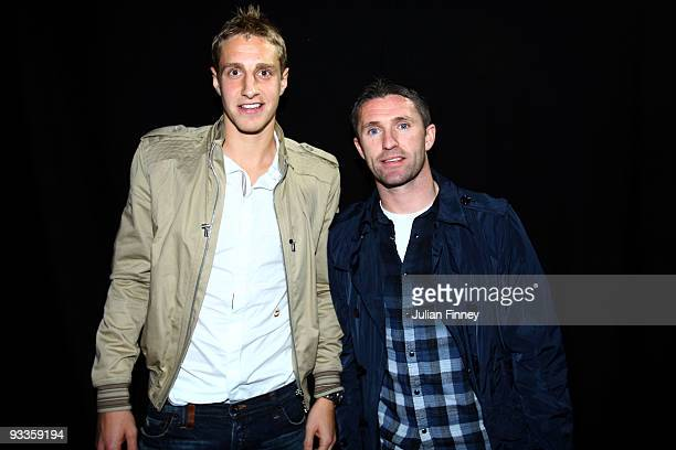 Michael Dawson and Robbie Keane of Tottenham Hotspurs watch pose for a picture before Andy Murray of Great Britain play in the men's singles second...