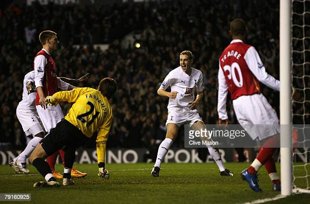 Michael Dawson of Tottenham celebrates as Nicklas Bendtner of Arsenal scores an own goal for Tottenham's 2nd during the Carling Cup Semifinal second...