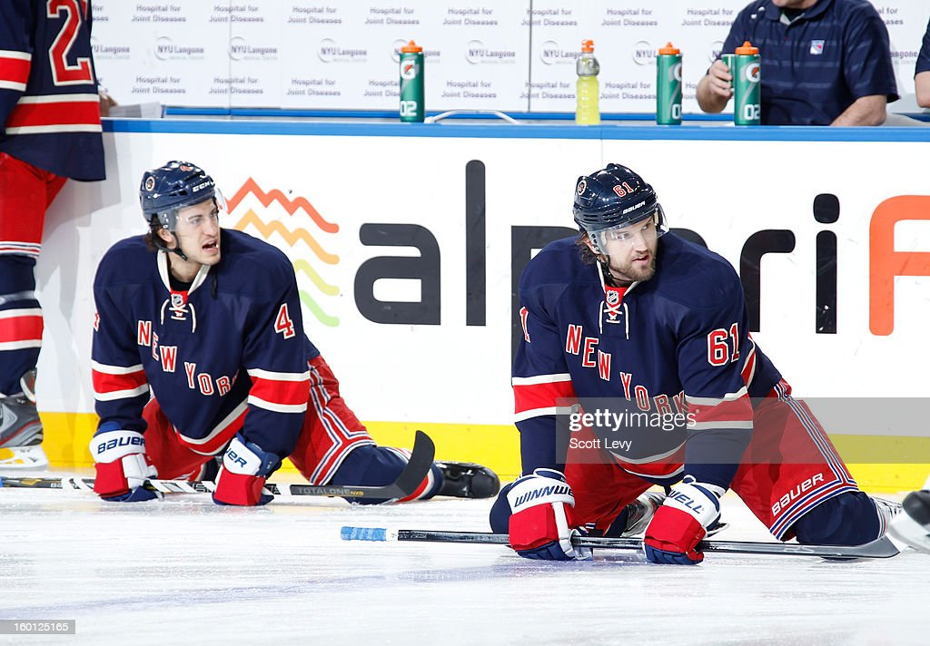 Michael Del Zotto #4 and Rick Nash #61 of the New York Rangers stretch during warm-ups prior to the game against the Toronto Maple Leafs at Madison Square Garden on January 26, 2013 in New York City.