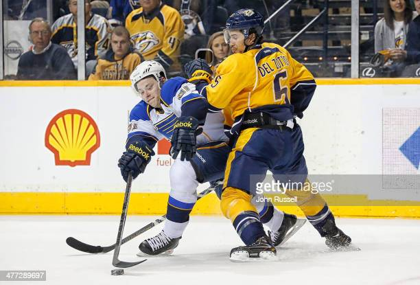 Michael Del Zotto of the Nashville Predators battles against Vladimir Tarasenko of the St Louis Blues at Bridgestone Arena on March 6 2014 in...