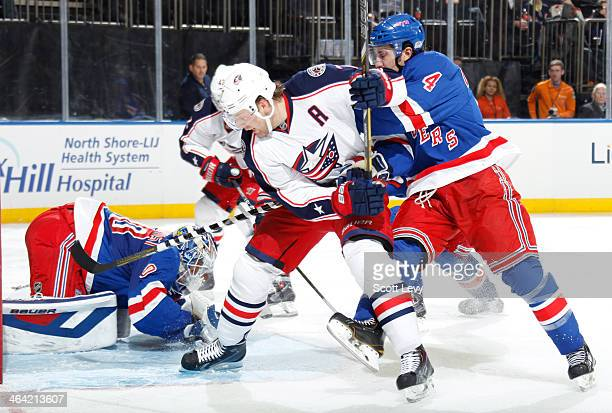 Michael Del Zotto of the New York Rangers and Jack Johnson of the Columbus Blue Jackets battle for position near the net at Madison Square Garden on...