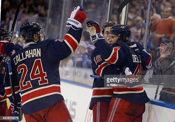 Michael Del Zotto of the New York Rangers celebrates his second period goal with Ryan Callahan and Derick Brassard of the New York Rangers during...