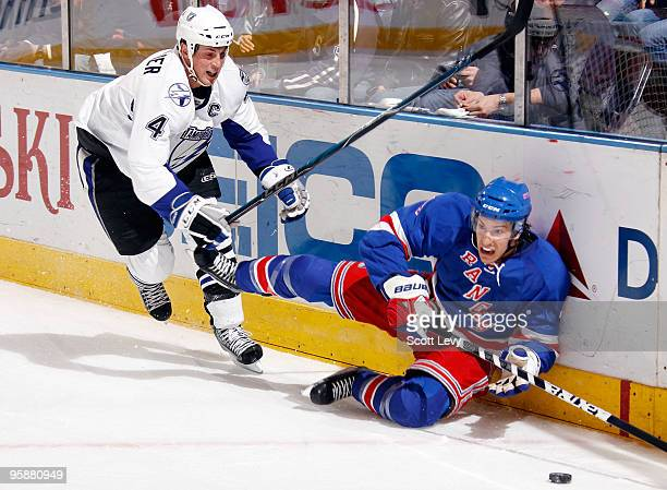 Michael Del Zotto of the New York Rangers falls to the ice while skating against Vincent Lacavalier of the Tampa Bay Lightning on January 19 2010 at...