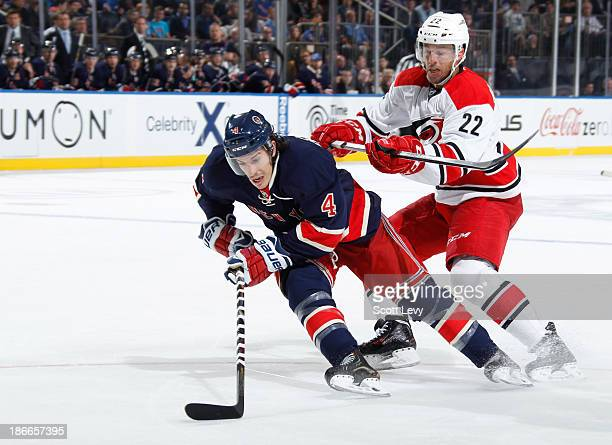 Michael Del Zotto of the New York Rangers is knocked down by Manny Malhotra of the Carolina Hurricanes at Madison Square Garden on November 2 2013 in...
