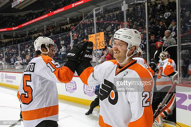 Michael Del Zotto of the Philadelphia Flyers high fives teammate Claude Giroux as they celebrate a 30 shutout over the Winnipeg Jets at the MTS...