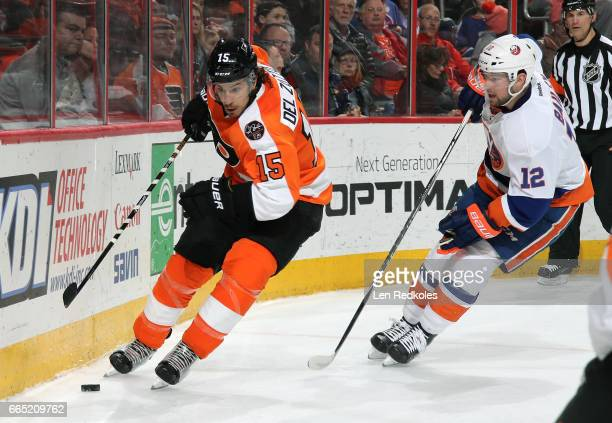 Michael Del Zotto of the Philadelphia Flyers skates the puck along the boards against Josh Bailey of the New York Islanders on March 30 2017 at the...