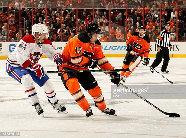 Michael Del Zotto of the Philadelphia Flyers takes the puck as Lars Eller of the Montreal Canadiens defends in the overtime period on October 11 2014...