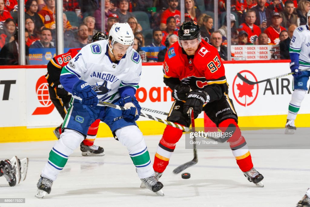 Michael Del Zotto #4 of the Vancouver Canucks and Sam Bennett #93 of the Calgary Flames battle for the puck in a NHL game against the Vancouver Canucks at the Scotiabank Saddledome on December 09, 2017 in Calgary, Alberta, Canada.