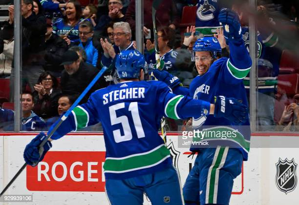 Michael Del Zotto of the Vancouver Canucks is congratulated by teammate Troy Stecher after scoring during their NHL game against the Minnesota Wild...