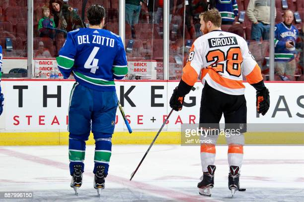 Michael Del Zotto of the Vancouver Canucks stands with former teammate Claude Giroux of the Philadelphia Flyers during warmup before their NHL game...