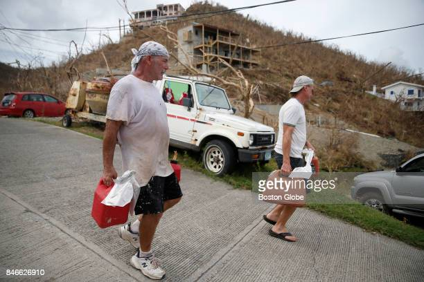 Michael Delle Chiaie who is originally from Salisbury MA but lives on St John carries gas for his generator alongside his neighbor Greg Kinslow after...