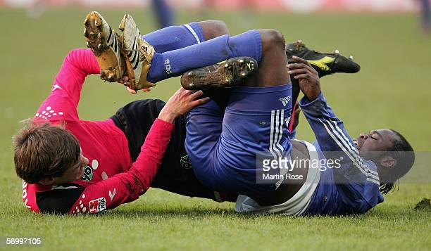 Michael Delura of Hannover and Gerald Asamoah of Schalke tangle on the pitch during the Bundesliga match between Hanover 96 and FC Schalke 04 at the...