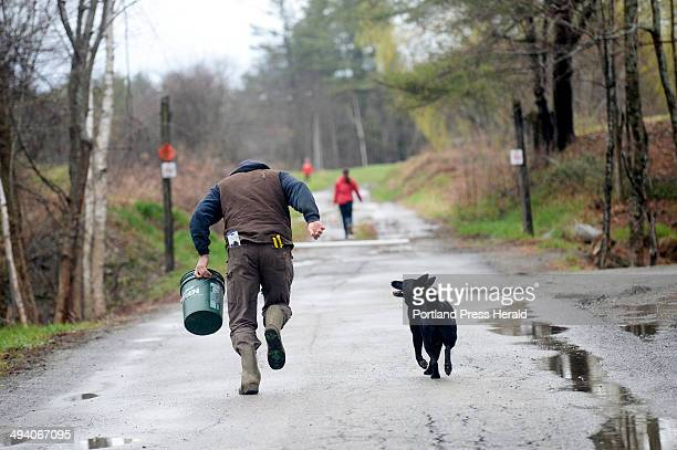 Michael Dennett runs with a bucket of feed towards the field where a pig got loose while he was moving his animals from the farm in Bremen to the...