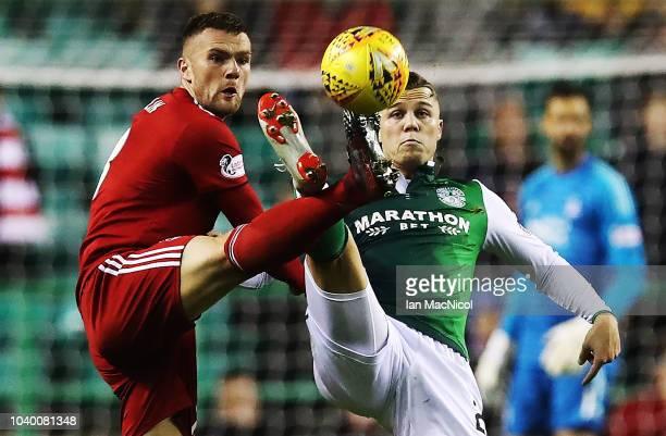 Michael Devlin of Aberdeen vies with Florian Kamberi of Hibernian during the Betfred Scottish League Cup Quarter Final match between Hibernian and...
