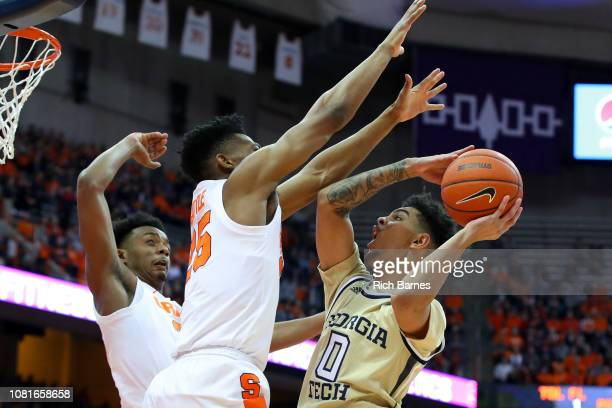 Michael Devoe of the Georgia Tech Yellow Jackets shoots the ball against the defense of Tyus Battle and Elijah Hughes of the Syracuse Orange at the...