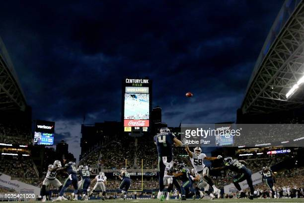 Michael Dickson of the Seattle Seahawks punts the ball against Kyle Wilber of the Oakland Raiders in the second quarter during their preseason game...