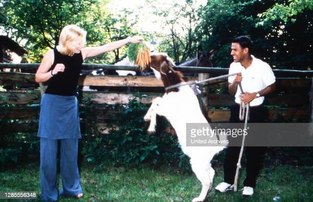 Michael Dierks und Diana Staehly, beide Schauspieler, füttern eine Ziege mit Karotten, Deutschland 1999.