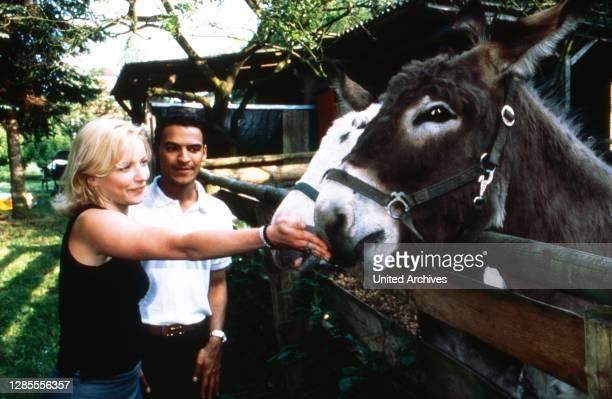 Michael Dierks und Diana Staehly, beide Schauspieler, füttern zwei Esel, Deutschland 1999.
