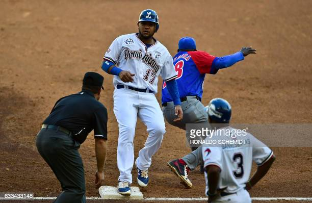 Michael Dimock of Tigres de Licey of the Dominican Republic slides safe into first base in a match against Alazanes de Granma of Cuba during the...