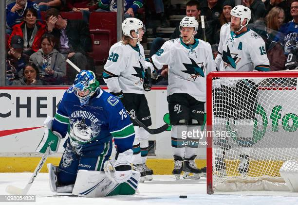Michael Dipietro of the Vancouver Canucks looks on dejected as Kevin Labanc of the San Jose Sharks is congratulated by teammates Joe Thornton and...