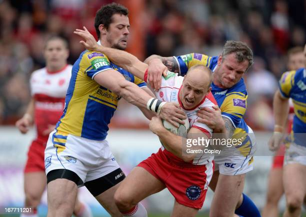 Michael Dobson of Hull KR is tackled by Ian Kirke and Jamie Peacock of Leeds during the Super League match between Hull Kingston Rovers and Leeds...