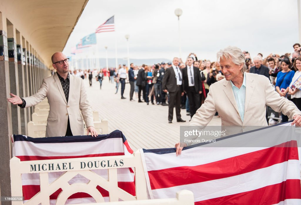 Michael Douglas and Steven Soderbergh pose next to the beach closet dedicated to them during a photocall on the Promenade des Planches for the movie 'Behind the Candelabra' during the 39th Deauville American Film Festival on August 31, 2013 in Deauville, France.