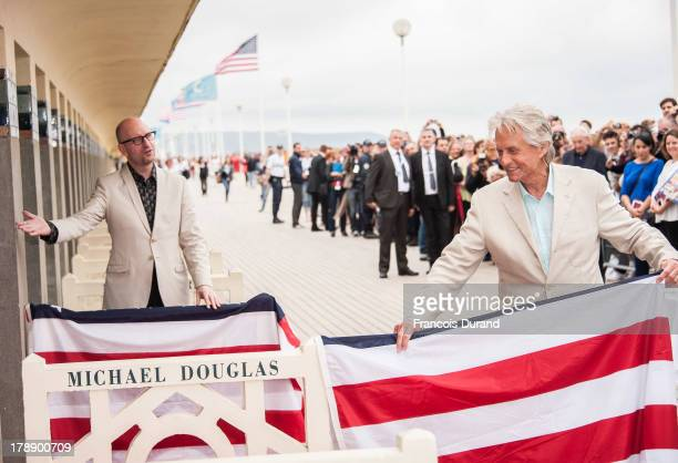 Michael Douglas and Steven Soderbergh pose next to the beach closet dedicated to them during a photocall on the Promenade des Planches for the movie...