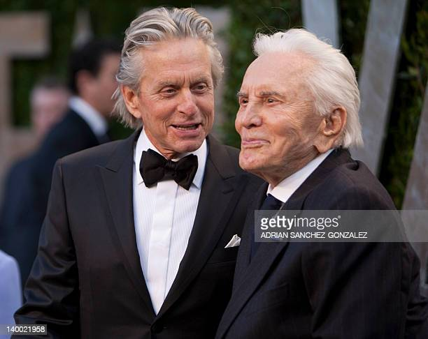 Michael Douglas greets his father Kirk Douglas on the carpet as they arrive at the Vanity Fair Oscar Party for the 84th Annual Academy Awards at the...