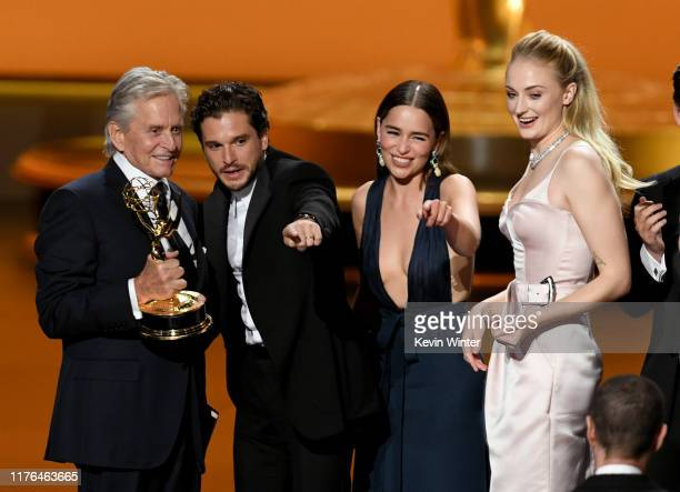 Michael Douglas presents the Outstanding Drama Series award for 'Game of Thrones' to Kit Harington, Emilia Clarke, and Sophie Turner onstage during...