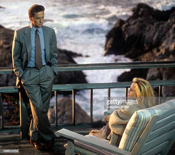 Michael Douglas standing in front of Sharon Stone on back porch in scene from the film 'Basic Instinct' 1992