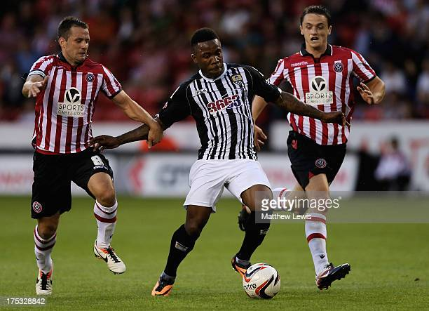 Michael Doyle and Stephen McGinn of Sheffield United tackle Mustapha Dumbuya of Notts County during the Sky Bet League One match between Sheffield...