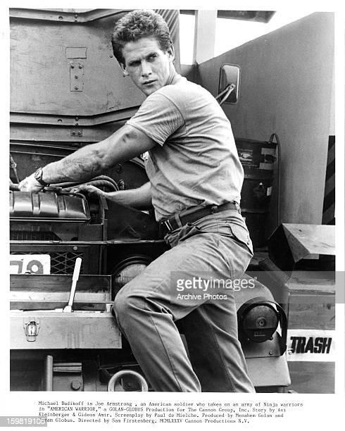 Michael Dudikoff working on vehicle in a scene from the film 'American Ninja' 1985