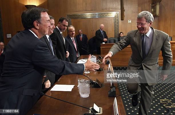 Michael Duke president and CEO of WalMart Stores Inc greets committee chairman US Sen Max Baucus prior to a hearing July 27 2011 in Washington DC The...