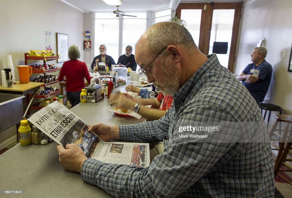 Michael Duke reads the Dothan Eagle newspaper with the headline 'Ethan Rescued' as he waits to eat lunch inside Marshall Sandwich Shop in the small downtown area of Midland City, Alabama February 5, 2013. The Midland City area has been gripped by a hostage situation when 5 year-old named Ethan was abducted from a school bus and held hostage for 6 days before being rescued when the FBI stormed the bunker killing suspect, Jimmy Lee Dykes.