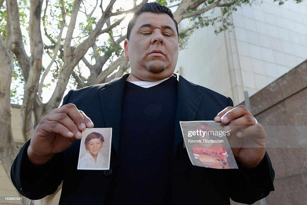 Michael Duran, who received nearly $1 million in a sex abuse settlement with the Roman Catholic Archdiocese of Los Angeles, holds up pictures of himself when he was a child after a news conference on March 14, 2013 in Los Angeles, California. Duran wants Pope Francis to defrock Cardinal Roger Mahony over his role in the cover up. Duran is one of four men who reached a nearly $10 million settlement against the Los Angeles Archdiocese, Mahony, and ex-priest Michael Baker, who is in jail after pleading guilty pleaded to a dozen sex charges.