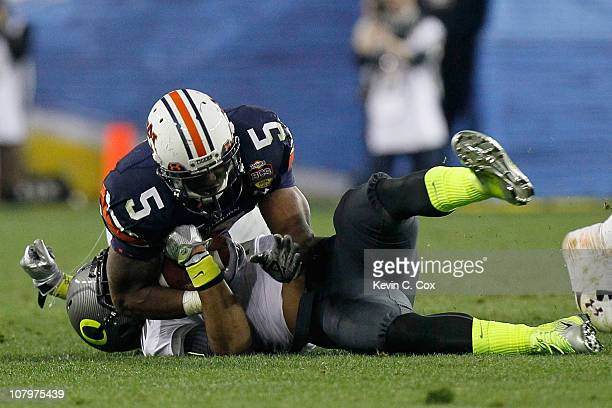 Michael Dyer of the Auburn Tigers rolls on top of Eddie Pleasant of the Oregon Ducks and runs for a 37-yard run late in the fourth quarter during the...