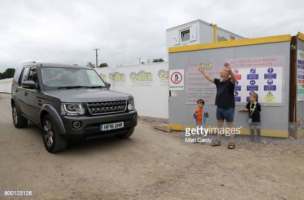 Michael Eavis and his grandsons Noah and George wave goodbye to David Beckham's car after the former footballer opened houses on Maggie's Farm in...