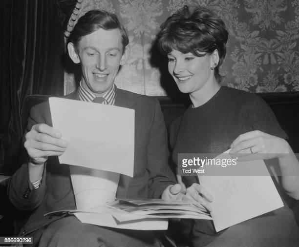 Michael Elliott , the new Artistic Director of the Old Vic in London, looks at photographs with actress Adrienne Corri during a reception at the...
