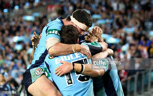 Michael Ennis and Kurt Gidley of the Blues celebrate a try by Anthony Minichiello during game two of the ARL State of Origin series between the New...