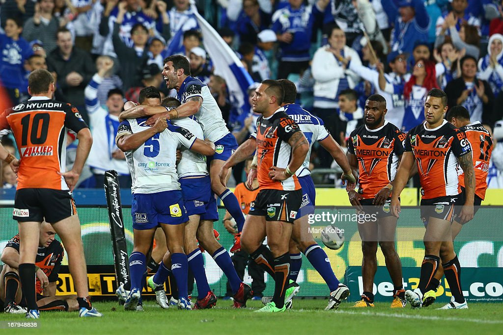 Michael Ennis of the Bulldogs jumps on his team mates as they celebrate with Tim Lafai of the Bulldogs is after he scored a try during the round eight NRL match between the Bulldogs and the Wests Tigers at ANZ Stadium on May 3, 2013 in Sydney, Australia.