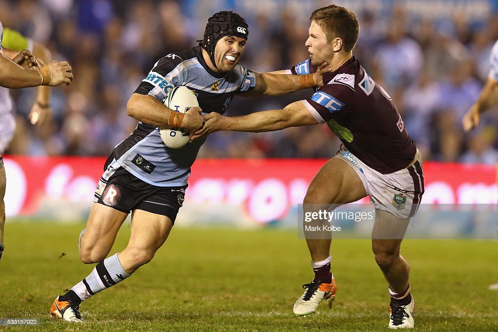 Michael Ennis of the Sharks fends off Matt Parcell of the Eagles during the round 11 NRL match between the Cronulla Sharks and the Manly Sea Eagles at Southern Cross Group Stadium on May 21, 2016 in Sydney, Australia.