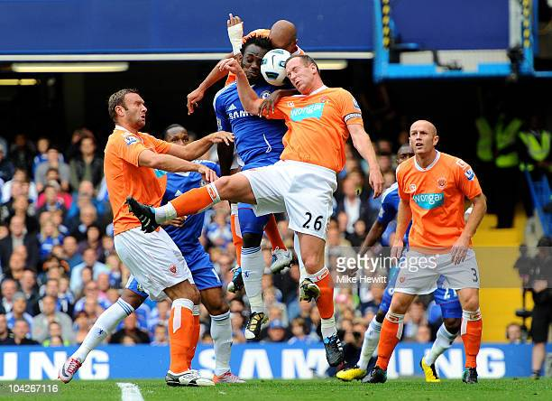 Michael Essien of Chelsea and Charlie Adam of Blackpool compete for a header during the Barclays Premier League match between Chelsea and Blackpool...