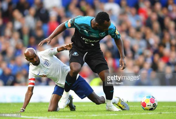 Michael Essien of Soccer Aid World XI battles with Sir Mo Farah of England during the Soccer Aid for UNICEF 2019 match between England and the Soccer...