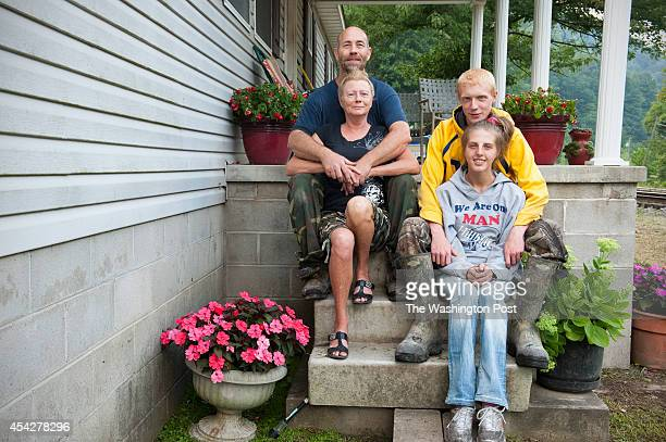 Michael Estep with his wife Vada their son Jobe and his livein girlfriend Kristen Goodman pose at their home August 13 2014 in Logan WV