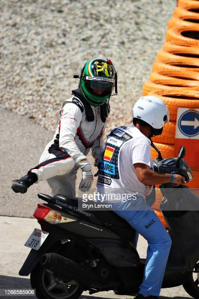 Michael Fassbender of Ireland and Porsche Motorsport rides a moped back to the paddock after retiring during the Porsche Mobil 1 Supercup at Circuit...
