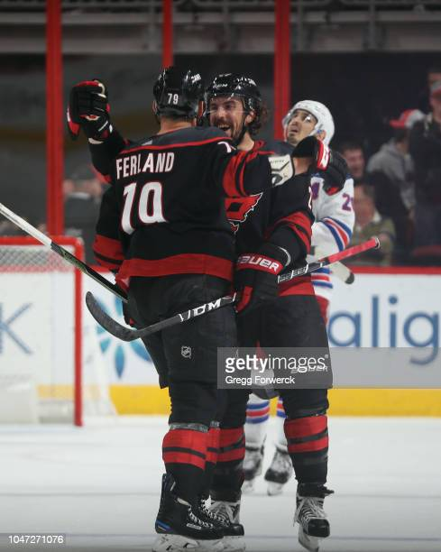Michael Ferland of the Carolina Hurricanes is congratulated by teammate Justin Faulk after scoring a goal during an NHL game against the New York...