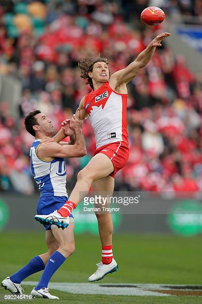 Michael Firrito of the Kangaroos and Kurt Tippett of the Swans compete for the ball during the round 22 AFL match between the North Melbourne...