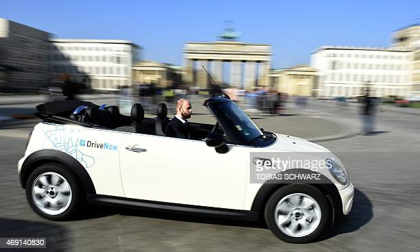 Michael Fischer press spokesperson of German carsharing company DriveNow poses in a convertible car of the company manufactured by brand Mini in...