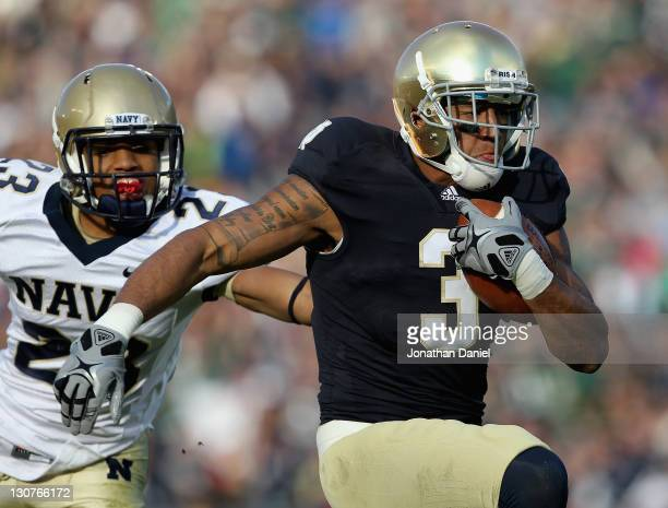 Michael Floyd of the Notre Dame Fighting Irish runs in front of Chris Ferguson of the Navy Midshipmen on a 56 yard touchdown catch at Notre Dame...